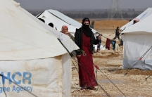 A Syrian refugee woman stands near her tent at the Al Zaatari refugee camp in the Jordanian city of Mafraq, near the border with Syria, January 15, 2015.