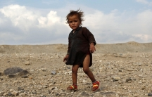 An internally displaced Afghan child stands outside a shelter outside Jalalabad city.