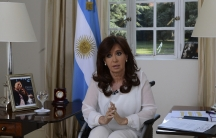 Argentina's President Cristina Fernández de Kirchner, sitting in a wheelchair, addresses the nation during a televised speech in Buenos Aires announcing an attempt to disband SIDE, the country's intelligence agency.