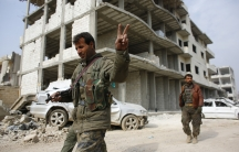 A fighter from the Kurdish People's Protection Units, or YPG, flashes a victory sign as he patrols the streets in the northern Syrian town of Kobane on January 28, 2015.