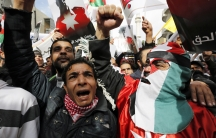 A protester dressed in a Jordanian flag joins others as they hold up pictures of Jordanian King Abdullah and Jordanian pilot Muath al-Kasaesbeh, while chanting slogans during a march after Friday prayers in downtown Amman February 6, 2015.