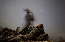 A US soldier of 2-12 Infantry Task Force Mountain Warrior takes a break during a night mission near Honaker Miracle camp at the Pesh valley of Kunar Province.