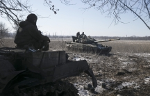 A member of a tank crew from the self-proclaimed Donetsk People's Republic Army sits on top of a tank at a checkpoint on the road from the town of Vuhlehirsk to Debaltseve on February 18, 2015.