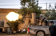 A fighter of the Kurdish People's Protection Units (YPG) fires an anti-aircraft weapon from Tel Tawil village in the direction of Islamic State fighters positioned in the countryside of the town of Tel Tamr in 2015.