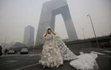 Kong Ning wears a wedding dress decorated with 999 face masks for her performance art work 'Marry the blue sky' as she poses for a photograph in front of the China Central Television (CCTV) Headquarters on a hazy day in Beijing November 19, 2014.