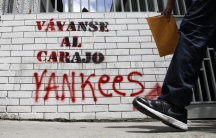"A man walks past graffiti which reads ""Yankees, go to hell"" in Caracas March 10, 2015. President Nicolas Maduro was seeking special decree powers from Venezuela's parliament on Tuesday in response to new US sanctions, drawing opposition protests of a powe"