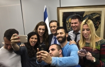 Isaac Herzog, at rear in the center, poses for a selfie with supporters of his center-left Zionist Union at their party headquarters in Tel Aviv on March 16, 2015.