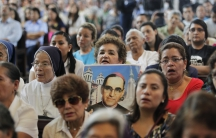 A woman holds a picture of late Archbishop Oscar Arnulfo Romero during a Mass to commemorate the 35th anniversary of his assassination in San Salvador on March 24.