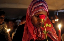 A woman holding a rose prays during a Nairobi memorial vigil following an attack by gunmen at Kenya's Garissa University College.