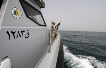 A Saudi border guard watches as he stands in a boat off the coast of the Red Sea on Saudi Arabia's maritime border with Yemen, near Jizan April 8, 2015