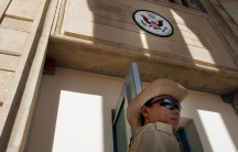A private security guard stands at the front entrance of the American Embassy building in Iraq inside the green zone in Baghdad in 2004.