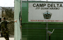 Soldier closes gate as military tribunals continue At Guantanamo Bay.