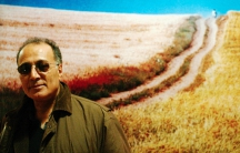 """Iranian film director Abbas Kiarostami poses in front of a poster for his film """"The Wind Will Carry Us"""" at the Portuguese film museum in Lisbon February 27, 2004."""