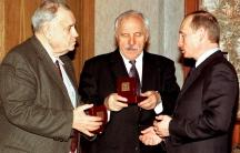 Russian President Vladimir Putin giving 75th birthday presents to actor Mikhail Ulyanov (C) and movie director Eldar Ryazanov (L) back in 2002