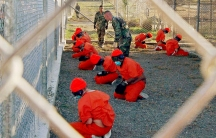Detainees in orange jumpsuits sit in a holding area watched by military police at Guantanamo Bay's Camp X-Ray in 2002.