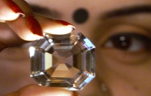 A woman holds a replica of the Koh-i-Noor diamond, during a diamond exhibition in Kolkata in 2002.