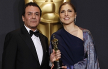 """Anousheh Ansari and Firouz Naderi pose with the Oscar they accepted on behalf of Asghar Farhadi, who won the Best Foreign Language Film for """"The Salesman""""."""
