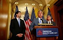 Three men standing at a podium