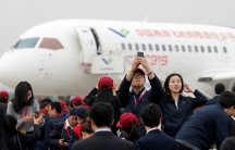 Attendees take photos in front of a Chinese C919 passenger jet after its first flight at Pudong International Airport in Shanghai.
