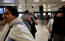 International passengers embrace family members as they arrive at Washington Dulles International Airport after the Trump administration's travel ban was allowed back into effect pending further judicial review, in Dulles, Virginia, U.S., June 29, 2017.