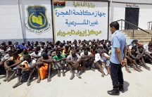 Detained migrants sit at a makeshift detention facility at Tajoura, Libya, earlier this month