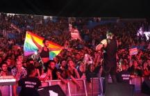A fan of  Mashrou' Leila holds a rainbow flag during their concert