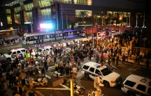 Overhead shot of crowd flanked by police SUVs, evening time