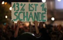 """A demonstrator holds a poster reading """"13 percent is a shame"""" during a protest against the anti-immigration party Alternative fuer Deutschland (AfD) after German general election in Berlin."""