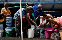People queue to fill containers with water from a tank truck at an area hit by Hurricane Maria in Canovanas, Puerto Rico.