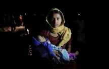 Rohingya refugees arrive under the cover of darkness by wooden boats from Myanmar to the shore of Shah Porir Dwip, in Teknaf, near Cox's Bazar in Bangladesh, Sept. 27, 2017.