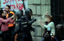 Riot police grab at a woman near a polling station for the banned independence referendum in Barcelona, Spain, on Oct. 1, 2017.