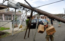 A member of the Puerto Rican National Guard dodges downed power cables as he hands out food and water