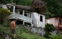 Months after Hurricane Maria slammed Puerto Rico, damage like this fallen tree on a roof in Utuado have yet to be repaired.