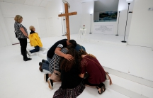 People pray in the First Baptist Church of Sutherland Springs where 26 people were killed in a shooting attack on November 5, 2017. The church was opened to the public as a memorial to those killed.