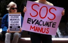 """A pink sign reading """"SOS EVACUATE MANUS"""" is held up by a protester."""
