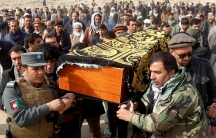 Afghan men carry the coffin of one of the victims of a car bomb attack in Kabul, Afghanistan January 28, 2018.