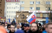 People hold up a cartoon of the new Slovak Prime Minister Peter Pellegrini during a march in Slovakia