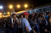 Migrants wait to board a train at the train station in Tovarnik, Croatia.