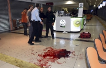 Israeli security personals stand next to blood on the floor, at the Beersheba central bus station where a Palestinian gunman went on a stabbing and shooting rampage, followed by a mob attacking a wrongly accused bystander, October 18, 2015.