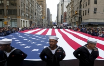 Members of the armed forces hold a US flag during the 2015 Veterans Day parade in New York