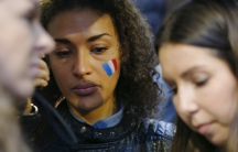 A woman wears the painted colours of France's national flag on her cheek during a candlelight vigil for the victims of the Paris attacks, in Sydney, Australia, November 14, 2015.