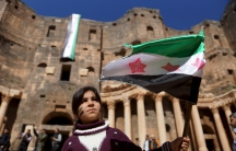 A Syrian girl waves an opposition flag during an anti-government protest inside a 2nd century Roman amphitheater in the historic Syrian southern town of Bosra al-Sham, in Deraa, Syria.