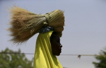 A woman carries dried grass on her head in a community for internally displaced people in Maiduguri, Nigeria March 9, 2016.
