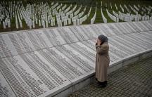 A woman prays near a war crimes memorial.
