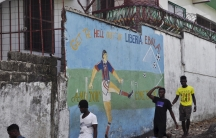 """Men walk by a mural that reads """"Get the hell of Liberia, Ebola! And don't come back"""" in Monrovia, Liberia, April 1, 2016."""
