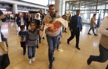 Family walks through airport, man in front hold infant