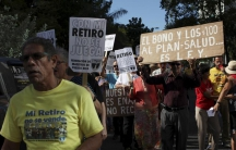 """Retired teachers from Puerto Rico's Teachers Federation protest against the underfunding of their pension system in San Juan, March 18, 2016. The sign reads """"Don't play with my retirement."""""""