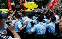 Police officers block protesters during a demonstration in Hong Kong against a visit by a top official from Beijing
