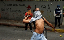 A demonstrator attempts to throw a bottle towards riot police officers during a protest called by university students against Venezuela's government in Caracas, Venezuela, June 9, 2016.