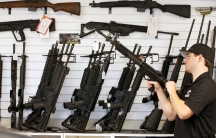 Salesman Ryan Martinez clears the chamber of an AR-15 at Ready Gunner, a gun store in Provo, Utah.